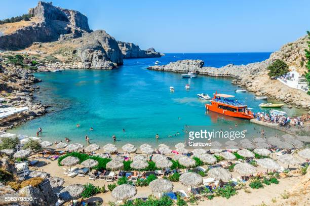 beautiful st. paul's bay in rhodes, greece - lindos stock photos and pictures