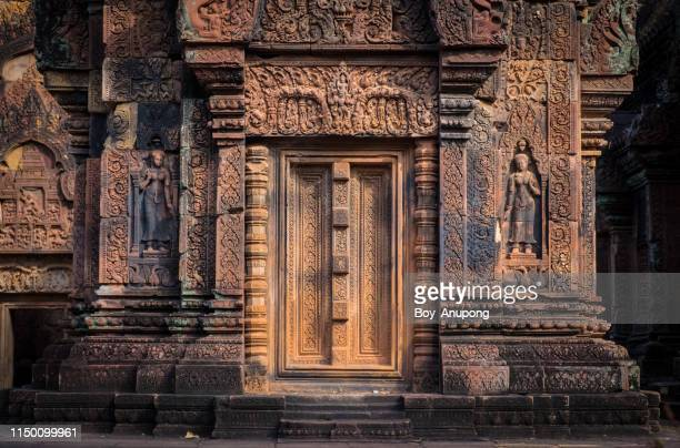 beautiful stone carving of banteay srei temple the most beautiful pink sandstone temple in siem reap, cambodia. - banteay srei stock pictures, royalty-free photos & images