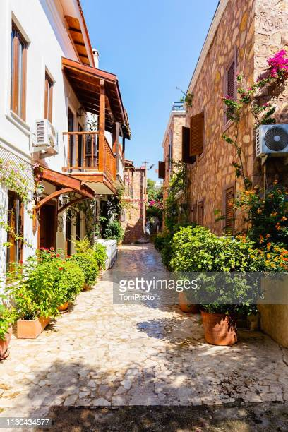 beautiful street of old town in turkey with flower pots and floral plants - kas stock pictures, royalty-free photos & images