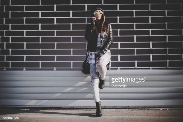 Beautiful street style girl on the metal fence