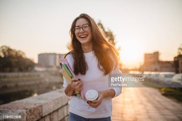 beautiful student girl with eyeglasses going home from school - 18 19 years stock pictures, royalty-free photos & images