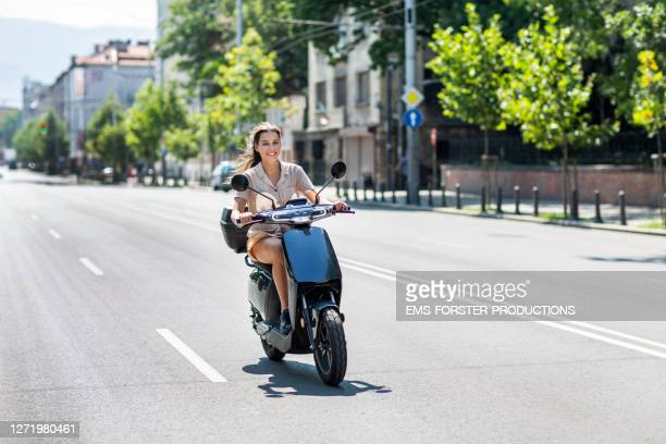 beautiful student is renting and riding an e-scooter in the city sofia - スクーター ストックフォトと画像