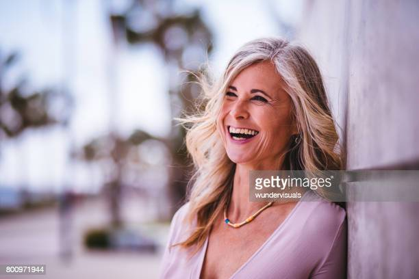 Beautiful stylish senior woman laughing leaning against wall outdoors