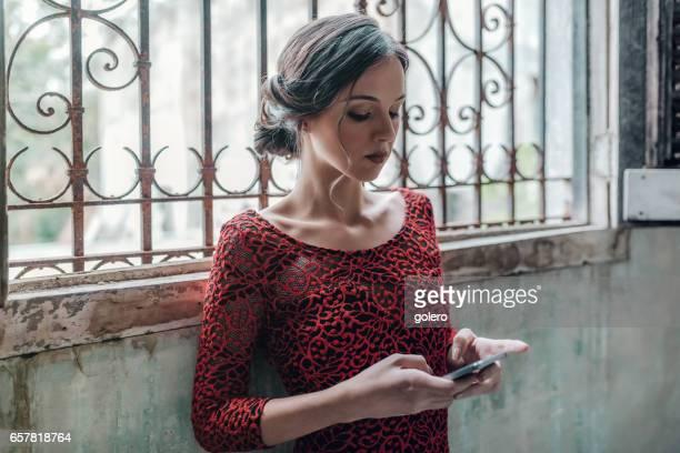beautiful stylish young cuban woman checking mobile at window
