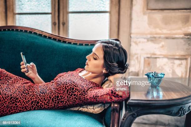 bella elegante cubana joven control móvil en el sofá - vestido de cóctel fotografías e imágenes de stock
