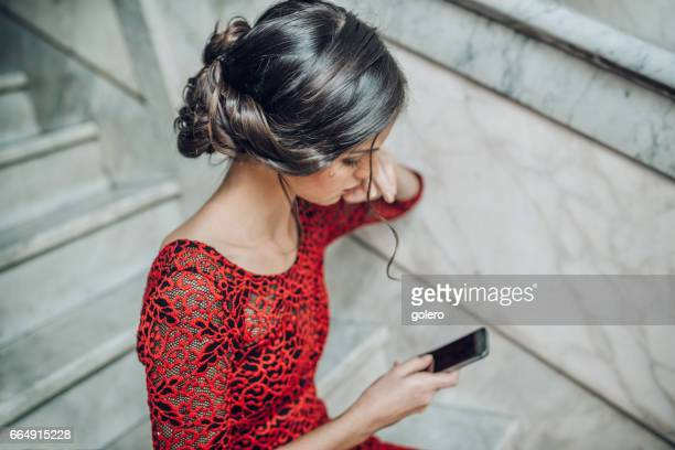 beautiful stylish young cuban woman checking mobile on stairs indoors