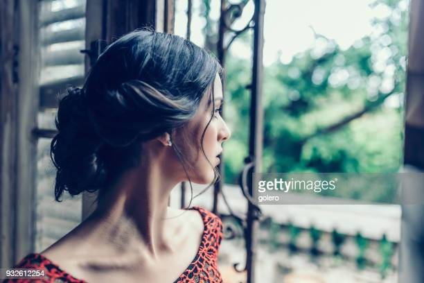 beautiful stylish young cuban woman llooking out of window - one young woman only stock pictures, royalty-free photos & images