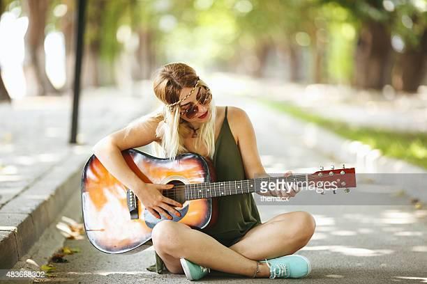 Schöne stilvolle Junge Frau spielt Gitarre