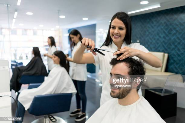beautiful stylist cutting customer's hair both smiling - hairstyle stock pictures, royalty-free photos & images
