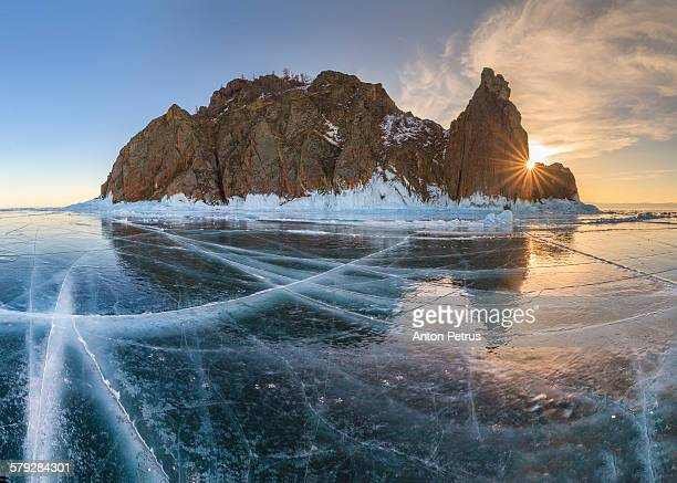 Beautiful sunny landscape with icy lake and rocks.