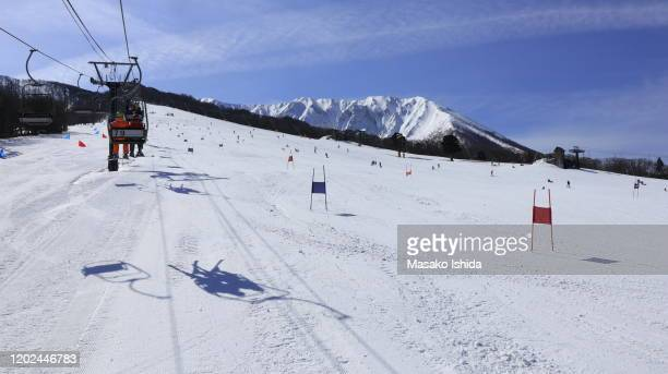 beautiful sunny view from ski lift going up to the top of snowy mountain against blue sky.people enjoy skiing and snowboarding on slope,snow covered mountain peaks in the background. daisen white resort,mt.daisen,tottori refecture,japan. - ski slalom stock-fotos und bilder