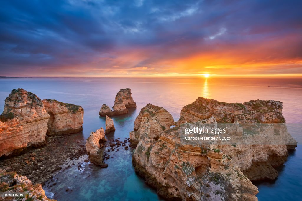 Beautiful sunrise at sea and rock formation in foreground : Photo
