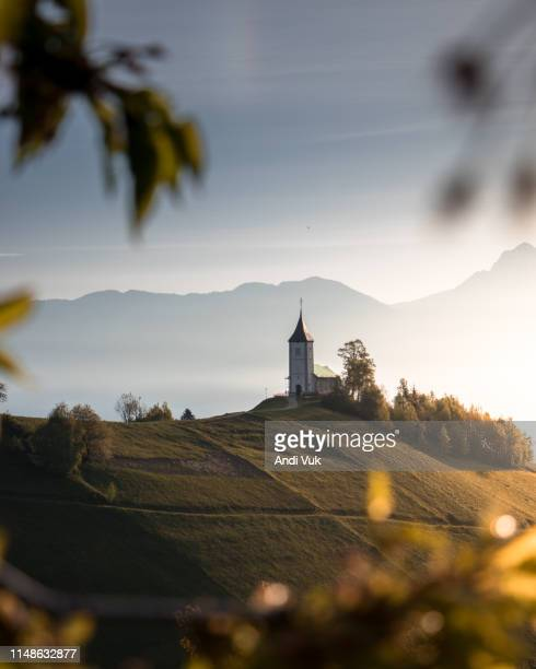 Beautiful sunrise landscape of church Jamnik in Slovenia on green hill