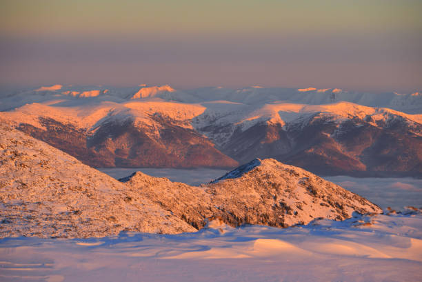 Beautiful sunrise on top of a mountain. Miment of freedom and adventure in a winter snowcapped peak.