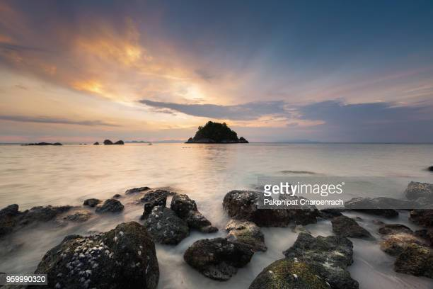 Beautiful sunrise on tropical white sand and rock near the Serendipity Beach Resort at Lipe Island, Satun Province, Thailand.