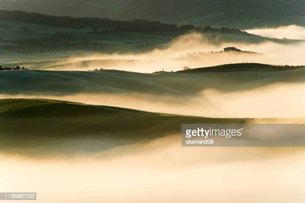 beautiful sunrise over  the mist and maedow at countryside of tuscany italy - cross processed stock pictures, royalty-free photos & images
