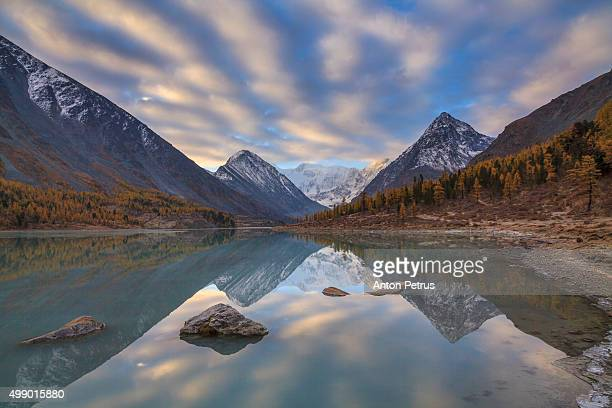 Beautiful sunrise over the mountain lake surrounded by high mountains