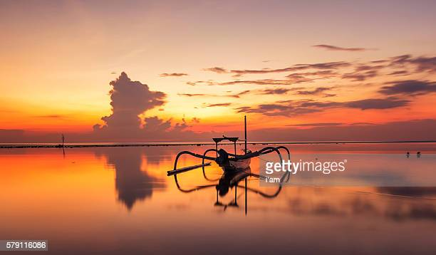 Beautiful Sunrise Scene in Bali, Indonesia. The rowboat or 'Jukung' is widely use as fishing boat by the local fisherman