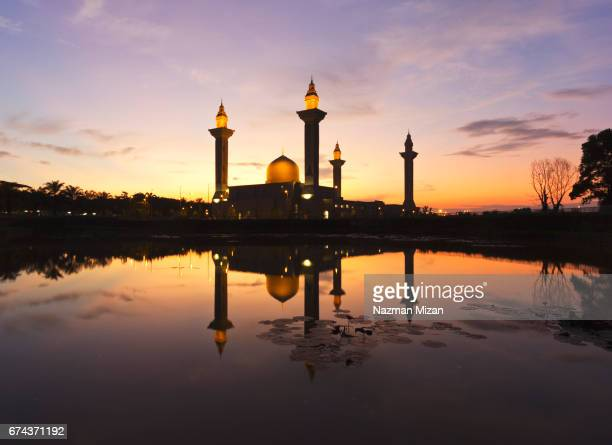 Beautiful sunrise with silhouetted mosque reflected in the water.