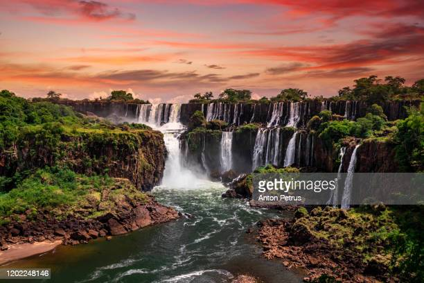 beautiful sunset at iguazu falls.  one of the new seven wonders of nature. traveling south america - waterfall stock pictures, royalty-free photos & images