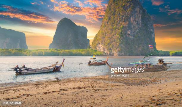 beautiful sunset at tropical sea with long tail boat in south thailand - southeast stock pictures, royalty-free photos & images