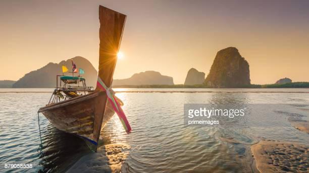 wunderschöner sonnenuntergang am tropischen meer mit einheimischem boot in süd-thailand - asiatisches langboot stock-fotos und bilder