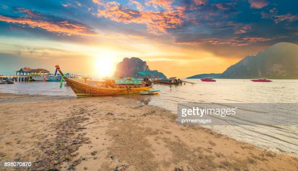 beautiful sunset at tropical sea with long tail boat in south thailand - indian ocean stock pictures, royalty-free photos & images