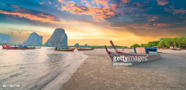 beautiful sunset at tropical sea with long tail boat in south thailand - tailandia foto e immagini stock
