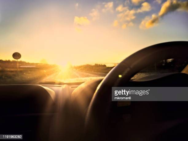 beautiful sunset from the driver's point while driving the car - car stock pictures, royalty-free photos & images