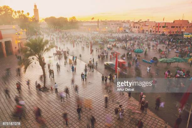 Beautiful sunset in the Jemaa El Fna square in the city of Marrakech with bustle activity, street food market lights and colorful sky, picture taken during travel vacations in Morocco.