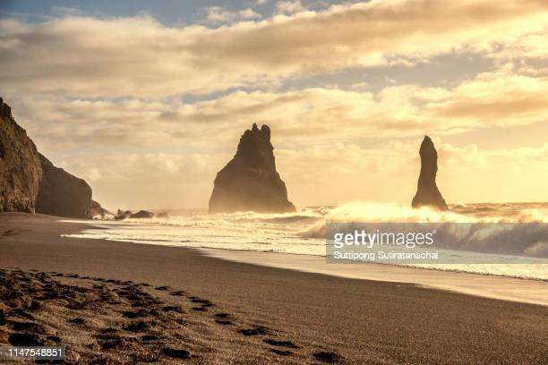 beautiful sunset landscape view of the black sand beach of reynisfjara and the mount reynisfjall  in vik the southern coast of iceland. - punalu'u_beach stock pictures, royalty-free photos & images