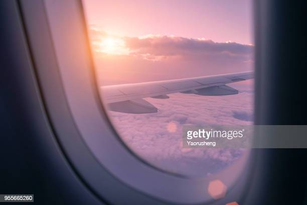 beautiful sunset  look through airplane window - flying stock photos and pictures