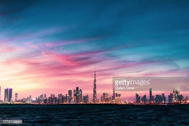 hermosa puesta de sol sobre la vista de los monumentos de dubái desde el puerto del arroyo dubai - paisajes de emiratos arabes fotografías e imágenes de stock