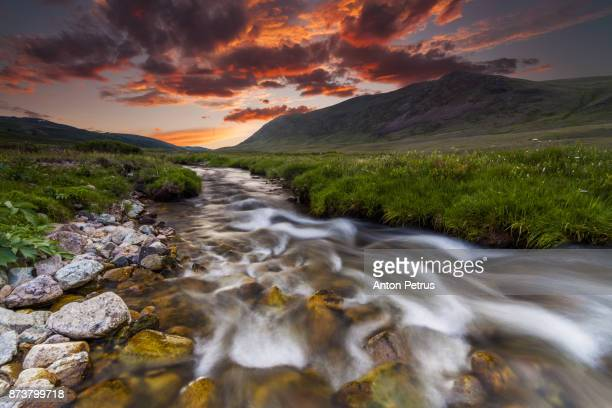 Beautiful sunset over the mountain river in summer.