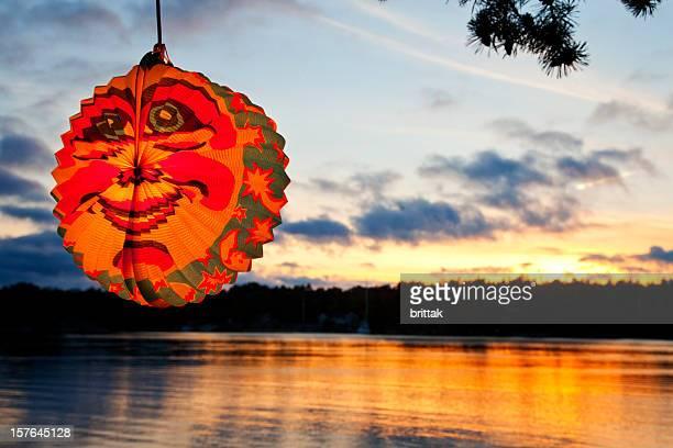 Wunderschöner Sonnenuntergang über dem Wasser in Stockholm Arcipelago mit Papierlaterne.
