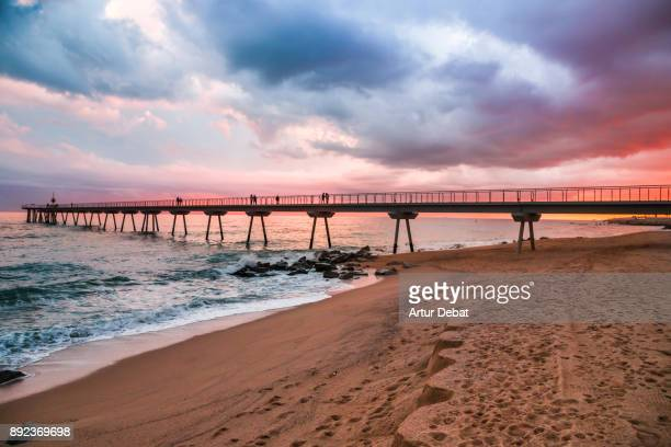 Beautiful sunset picture with burning sky in winter time in Barcelona shoreline with stunning pier going over the Mediterranean Sea.