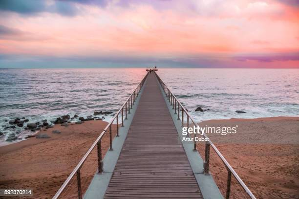 Beautiful sunset picture with burning sky in winter time in Barcelona shoreline with stunning pier going over the Mediterranean Sea with vanishing point and infinity landscape during burning sky sunset in a unique and minimal place.