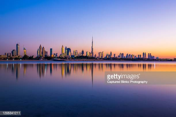 dubai uae - december 2019: beautiful sunset showing the dubai skyline with mirrorlike reflections in the lake - dubai stockfoto's en -beelden