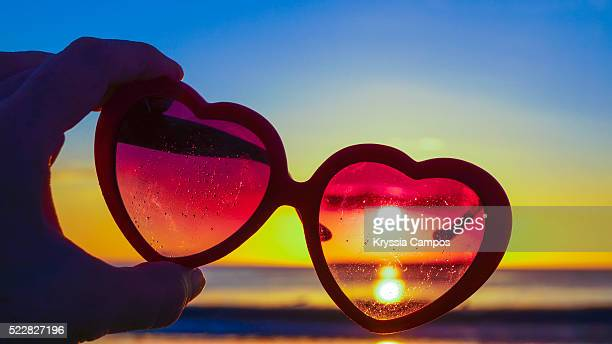 beautiful sunset through heart-shaped sunglasses on beach - flamingo heart stock pictures, royalty-free photos & images