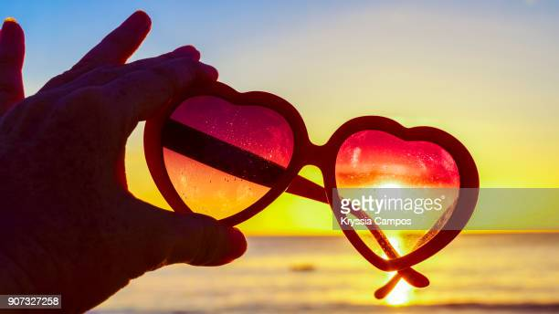 beautiful sunset through heart-shaped sunglasses on beach - klimaschutz stock-fotos und bilder