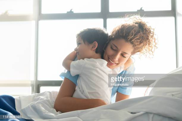beautiful sweet little boy hospitalized in the pediatrics ward hugging young nurse - cute nurses stock pictures, royalty-free photos & images