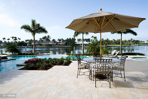 beautiful swimming pool and patio overlooking waterway - naples florida stock pictures, royalty-free photos & images