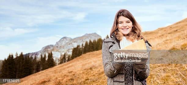 beautiful swiss woman presenting cheese in alpine mountains - zwitserse kaas stockfoto's en -beelden