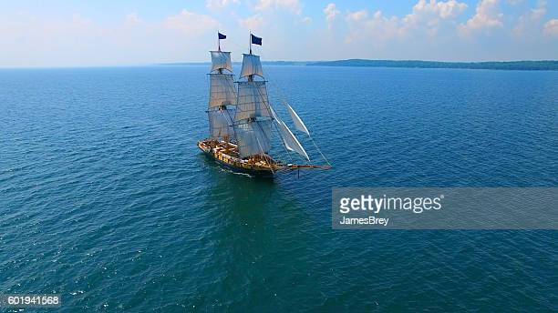 beautiful tall ship sailing deep blue waters toward unseen adventures - pirate ship stock photos and pictures