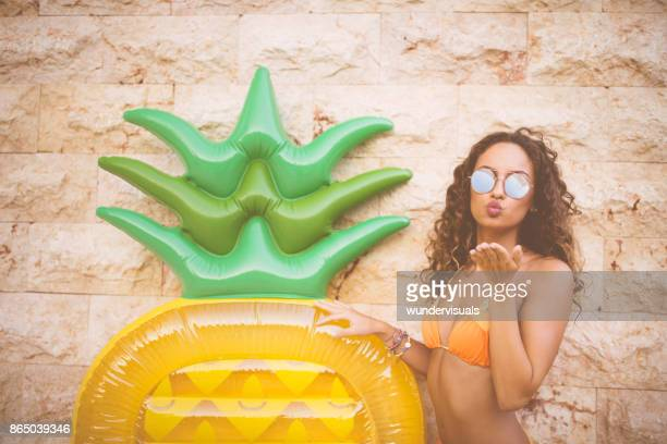 Beautiful tanned woman holding summer inflatable and sending air kiss
