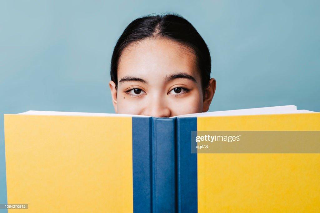 美しい十代の少女は、幸せの教科書の後ろに彼女の笑顔を非表示に : ストックフォト