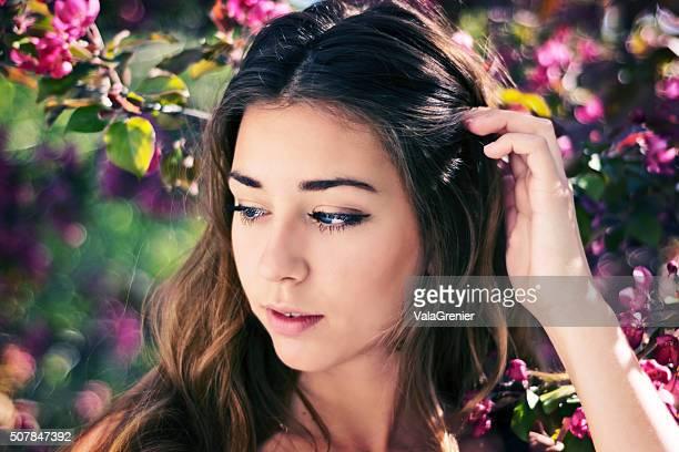 Belle Teen fille fleurs de pommier, en tirant les cheveux en arrière.
