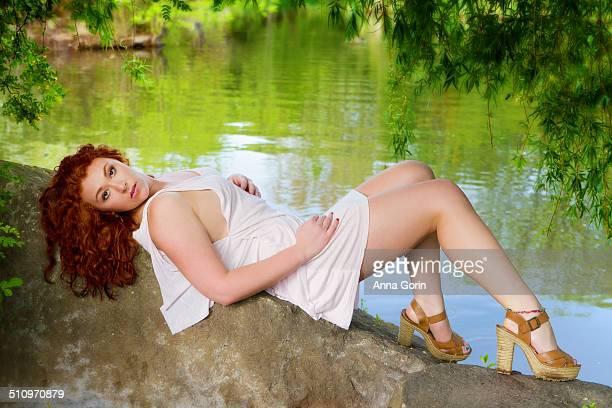 beautiful teen redhead in dress reclining by water - miniklänning bildbanksfoton och bilder