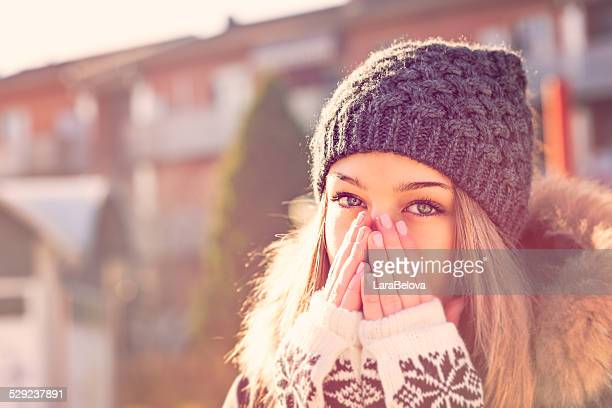 Beautiful teenage girl heats up hands