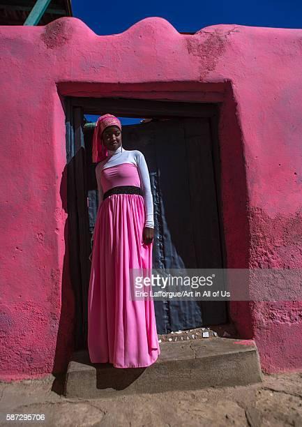 Beautiful teenage girl in pink in front of a doorway, harari region, harar, Ethiopia on March 4, 2016 in Harar, Ethiopia.